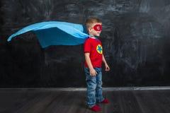 Супергерой мальчика в маске голубой накидки красной и красная футболка с звездой Стоковое Фото