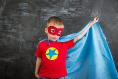 Супергерой мальчика в маске голубой накидки красной и красная футболка с звездой Стоковая Фотография RF