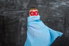 Супергерой мальчика в маске голубой накидки красной и красная футболка с звездой Стоковые Фото