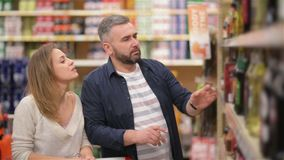 супермаркет покупкы пар счастливый Молодая семья выбирая вино от полок супермаркета акции видеоматериалы