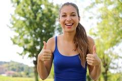 Супер женщина! Портрет девушки победителя показывая большие пальцы руки вверх положительно стоковое фото rf