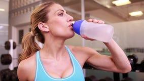 Супер женщина пригонки выпивая от бутылки с водой и усмехаться сток-видео