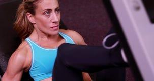 Супер женщина пригонки используя ногу утяжеляет машину видеоматериал