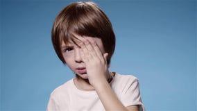 Супер замедленное движение затирания мальчика наблюдает плакать или утомлянная, голубая предпосылка видеоматериал