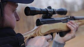 Супер конец-вверх человека во время съемки снайперской винтовки Взгляд от сверх ее плеча сток-видео