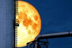 супер луна крови назад над масляным баком рафинадного завода силуэта стоковые изображения