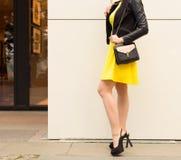 Супер модная длинн-шагающая девушка с внутри коротким желтым платьем, черные высокие пятки с большой черной сумкой делает ходить  Стоковая Фотография