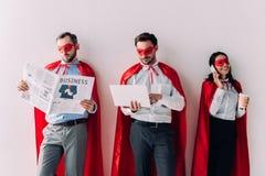 супер предприниматели с газетой, компьтер-книжкой и smartphone стоковое изображение
