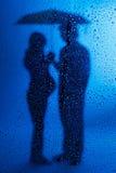 Супоросая повелительница и супруг стоя под дождем Стоковое Изображение RF
