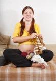 супоросая сидя женщина софы Стоковое Изображение