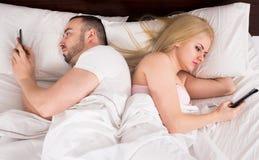 Супруги представляя с smartphones Стоковое Фото