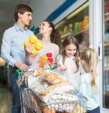 Супруги при 2 дет держа приобретения в магазине Стоковые Изображения