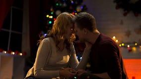 Супруг давая настоящий момент жене и целуя ее, празднующ годовщину на Xmas стоковые изображения rf