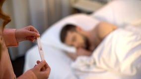 Супруг дамы готовя спать при положительный тест на беременность, принимая решениее стоковые изображения