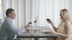 Супруг и жена имеют обедающий в ресторане, женщина говорит здравицу сток-видео