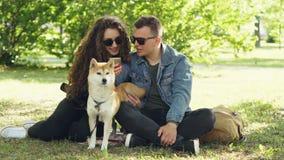 Супруг и жена используют smartphone отдыхая на лужайке в парке, наблюдая экране и говоря и суетясь собаке самомоднейше сток-видео