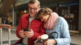 Супруг и жена на железнодорожном вокзале См. фото в умных телефоне и жизнерадостно смехе Памяти счастливого видеоматериал