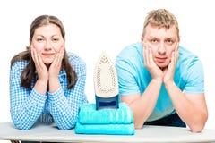 Супруг и жена представляя на утюжа доске при утюг, снимая на белизне Стоковое фото RF