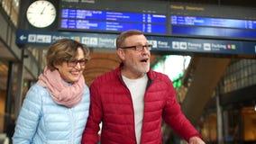Супруг и жена стоят на платформе железнодорожного вокзала, они смеются весело, человек кашляют в шутку, акции видеоматериалы