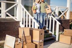 Супруг и жена стоя перед новым покупая домом с коробками стоковое изображение rf