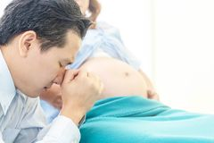 Супруг молит для его жены безопасной и здоровой для newborn деятельности стоковое изображение