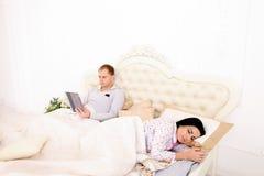 Супруг работает на таблетке пока жена спать в белой кровати Стоковая Фотография