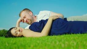 Супруг с беременной женой лежит на зеленой траве На фоне голубого неба сток-видео