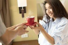 Супруг служит кофе в кровати к его жене и просыпаться она стоковые изображения rf
