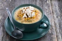 Суп мозоли с попкорном в керамической чашке на деревянном столе Стоковые Изображения