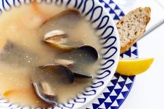 Суп морепродуктов с мидиями, креветками и рыбами в белом шаре с голубым орнаментом в ресторане стоковое фото