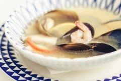 Суп морепродуктов с мидиями, креветками и рыбами в белом шаре с голубым орнаментом в ресторане стоковое изображение