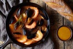 Суп морепродуктов рыб буйабес с креветками, мидиями томатом, омаром Соус Rouille Деревенская предпосылка стиля Плоское положение Стоковые Фото