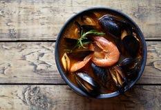 Суп рыб буйабес с креветками, мидиями томатом, омаром Деревенская предпосылка стиля Плоское положение Стоковая Фотография RF