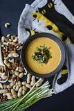 Суп сливк тыквы с травами и гайками, служил в темном шаре Свойственная и здоровая еда Вегетарианское блюдо r стоковое фото rf