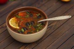 Суп Солянки с лимоном, мясом, соленьями, томатным соусом и блюдом Солянкой оливок традиционным русским стоковые фото