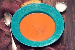 Суп томата в зеленом блюде с хлебом на коричневой предпосылке Стоковые Фотографии RF