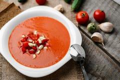 Суп томата гаспачо в белой ложке шара на полотенце на предпосылке деревянных доск Стоковые Изображения