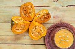 Суп тыквы бака украшенный с отрезанными частями желтых тыквы и семян на деревянной предпосылке Традиционная еда осени Стоковые Фотографии RF