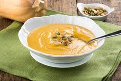 Суп тыквы в белой плите на деревянном столе стоковое фото rf