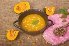 Суп тыквы в глиняном горшке с свежими тыквами Стоковые Изображения