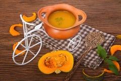 Суп тыквы в глиняном горшке с свежими тыквами Стоковая Фотография