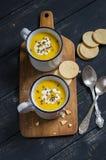 Суп тыквы в керамических кружках на деревянной поверхности Стоковые Изображения RF