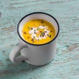 Суп тыквы в керамических кружках на деревянной поверхности Стоковые Изображения