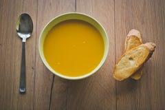 Суп тыквы и моркови с шутихами и петрушкой на деревянной предпосылке с ложкой и провозглашанными тост кусками хлеба Стоковые Изображения