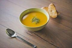 Суп тыквы и моркови с шутихами и петрушкой на деревянной предпосылке с ложкой и провозглашанными тост кусками хлеба Стоковая Фотография RF