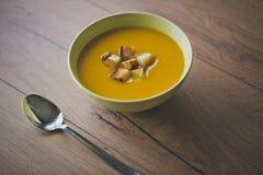 Суп тыквы и моркови с шутихами и петрушкой на деревянной предпосылке с spoun Стоковые Фото