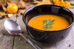 Суп тыквы осени в черном шаре на естественном столе стоковая фотография