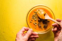 Суп тыквы с семенами и гренками на желтых таблице и ложке в руке Стоковые Фотографии RF