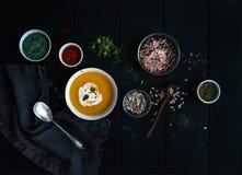 Суп тыквы с сливк, семена и различные специи в деревенском шаре металла над grunge чернят предпосылку Взгляд сверху Стоковое Изображение RF