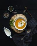 Суп тыквы с сливк, семена и специи в деревенском шаре металла над grunge чернят предпосылку Взгляд сверху Стоковая Фотография RF